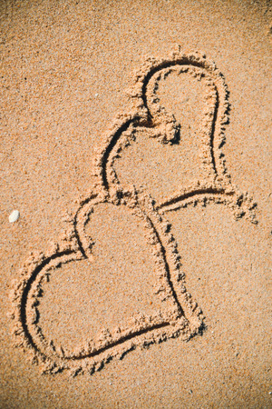 evoke: Two hearts drawn on the sand of a beach background