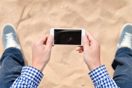 selfy: Top view closeup on man holding phone on the beach outside background, sunny day
