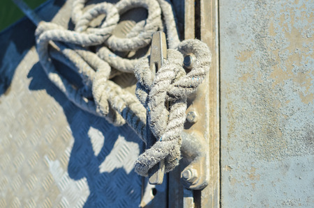 mooring bollard: Closeup on mooring bollard with rope tied on pier by the sea outdoors background