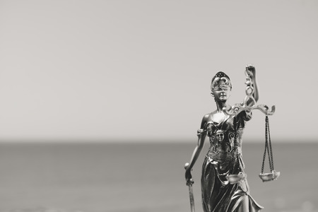 judicature: Justice Themis goddess sculpture on bright sky copy space background. Black and white image
