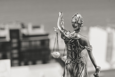 judicature: Back view of justice, femida or themis goddess sculpture on light copy space background. Black and white image