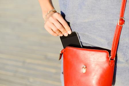 Closeup photo of stylish female taking cellphone out of handbag, sunny outdoors background Stockfoto