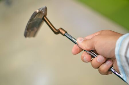 Closeup on person holding golf club in hand, shop background Stock Photo