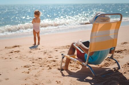 Back view of small cute child playing tablet computer during summer vacation on beach sunny outdoors background