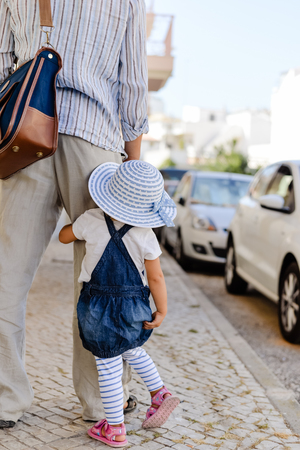 Father with daughter walk along an urban road carrying briefcase, rear view