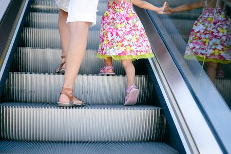 bajando escaleras: Vista trasera de la hermosa chica de niño caminar con la madre, escaleras mecánicas escaleras fondo, vista de cerca. Escalera móvil en el centro comercial, edificio de oficinas