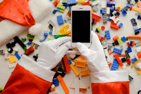 Joyful time and Santa Claus holding mobile smartphone with blank screen background, Closeup image