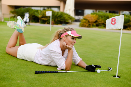 Portrait of beautiful woman relaxing during playing golf on a green field outdoors background Stock Photo