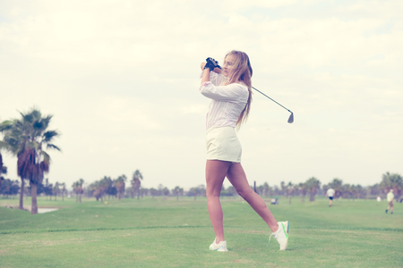 Fashion sport style beautiful woman standing holding golf club on outdoors green field background
