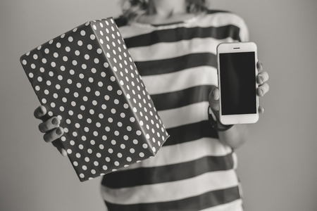package sending: Female holding using a smartphone and shopping box. Black and white closeup view