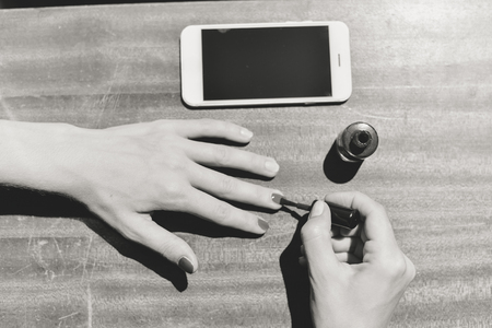 Top view on cell phone and hands doing manicure. Close up table mockup background. Black and white image