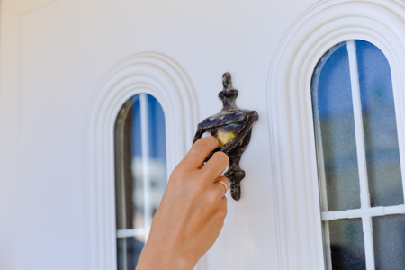 Closeup on hand on beautiful door knocker, elegant design light background
