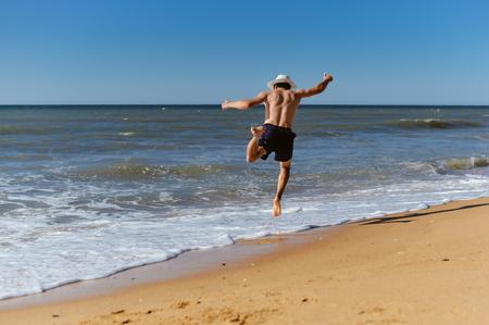 beach hunk: Back view of joyful man on the beach sunny blue sky outdoors background Stock Photo