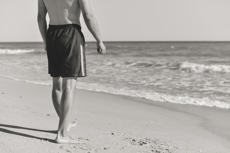 beach hunk: Back view of joyful man on the beach sunny outdoors background. Black and white image