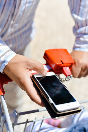 Person order buying via smart phone application, shop cart department store mall background. Closeup top view mock up background photo Stock Photo