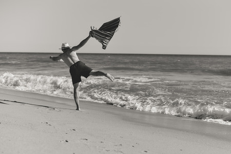 beach hunk: Back view of man jumping of joy on the beach sunny outdoors background