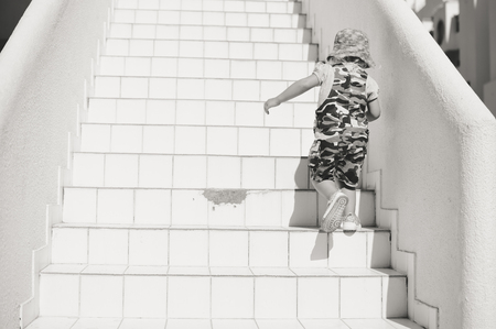 stair climber: Back view of the small child walking up the stairs on real estate sun light background