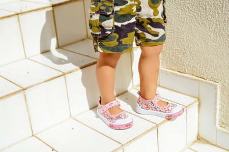 stair climber: Small child walking down the stairs on real estate sun light background Stock Photo