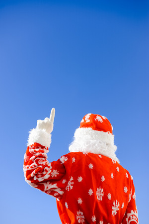 Santa Claus pointing finger at copy space background. Back view image Stock Photo