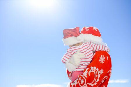 xmass: Joyful Santa Claus holding giftbox in hands on blue light sky outdoors background