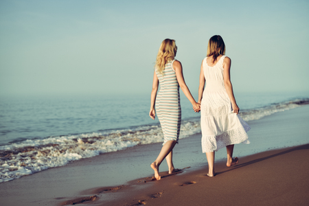 Back view of two woman on holiday travel vacation beach. Sunny ocean sky background