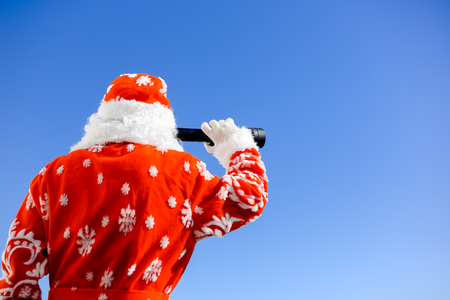 spying: Santa Claus looking through spy glass on sunny blue sky outdoors background