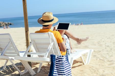 ビーチ両手空白の画面の背景を持つタブレット コンピューターに坐っている人。上から見たクローズ アップ広告プロモーション電子通信
