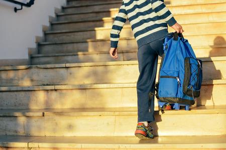 Widok z tyłu chłopca chodzącego po schodach na zewnątrz budynku w tle