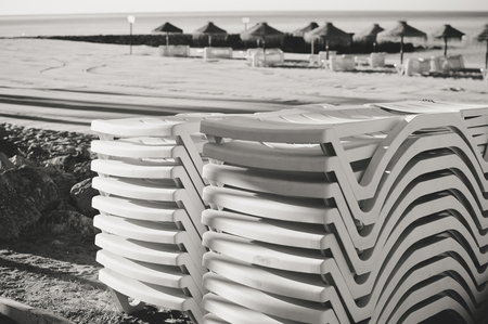 vocation: Holiday and vocation image with sandy beach, parasol and chairs on outdoors background. Black and white image