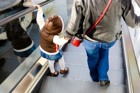 エスカレーターの背景に母と子は一緒の背面します。ショッピング モール、空港の旅行、愛ケア