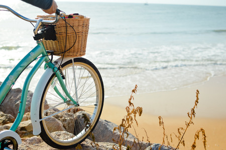 Person holding bicycle on natural beach outdoors background. Closeup image Фото со стока