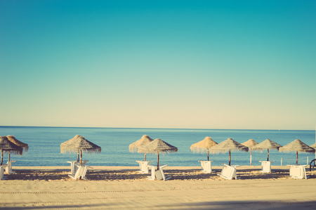 vocation: Holiday and vocation image with beach lounge and parasol on ocean sea outdoors sunny background