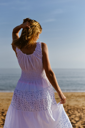 Back view of woman walking dancing on the sunny beach natural outdoors background. Travel vacation relaxation abroad lifestyle Stock Photo