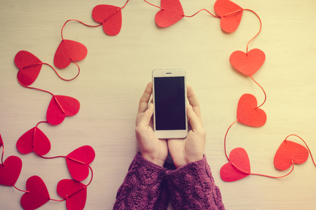 string top: Top view on woman hands holding mobile smartphone surrounded with string of love hearts. Flat lay style image Valentines day feelings background Stock Photo