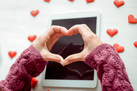 Top view on woman hands using mobile tablet computer surrounded with string of love hearts. Flat lay style image Valentines day feelings background