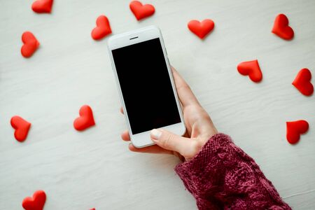 愛の心の背景にスマート フォンを保持している女性 写真素材