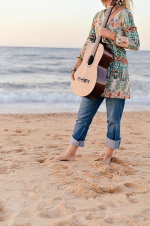 Elegant Beautiful Female Having Fun Playing Guitar On Sand Beach Outside Sunset Sky Background Photo