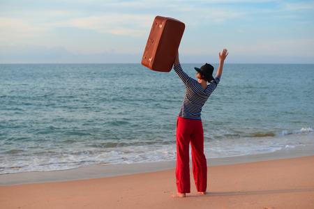 ビーチの屋外背景にスーツケースを持つ人の背面側