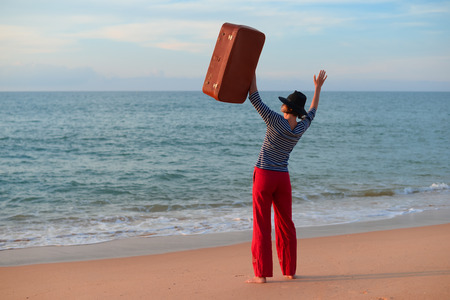 Back side view of person with suitcase on the beach outdoors background