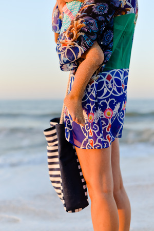 Back side view of mother and child walking on sandy beach sunset outdoors background