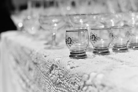 White table and row of beautiful glasses, celebration design set background Фото со стока