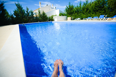 property ladder: Woman legs inside open air swimming pool blue surface background