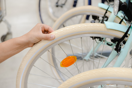 air pressure: Closeup on person hand checking bicycle tire, shop factory background. Stock Photo