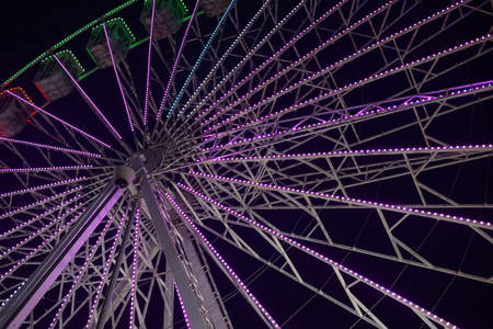 Colorful blurry lights of amusement park ferris wheel and rollercoaster on the night background Stock Photo