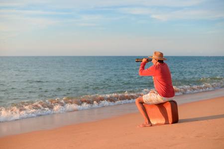 Back side view of man sitting holding spyglass looking at natural ocean water shore outdoors background. Traveler discovering journey, exploring escape or market opportunities. Sunny blue sky horizon