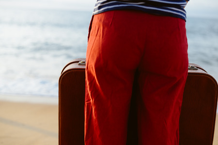 Closeup on blurry woman holding suitcase on the sea beach outdoors background. Traveler discovering journey, exploring escape or journey opportunities. Sunny water