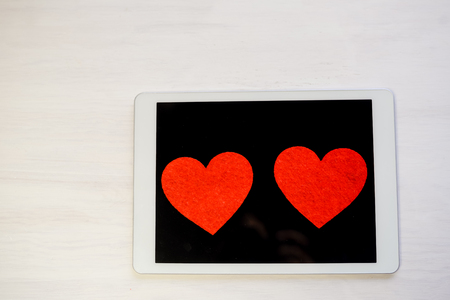 play date: Tablet PC Computer and Love Heart. Happy Emotional Celebration, Lovely Atmosphere Background Stock Photo