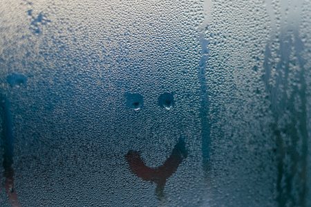 Happy smile drawn on the fogged glass window background. Close up image of condensated surface