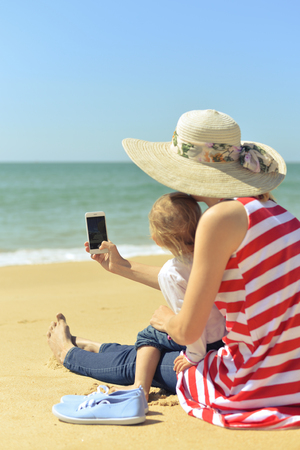 Back view of female with child taking selfie on smart phone at tropical beach on sunny background. Blue sky sea outdoors Stock Photo