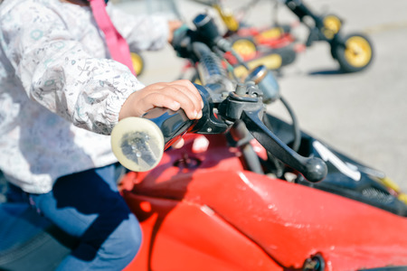 Algarve, Portugal - April 13, 2016: Small child riding a quad bike on sunny outdoors background, closeup
